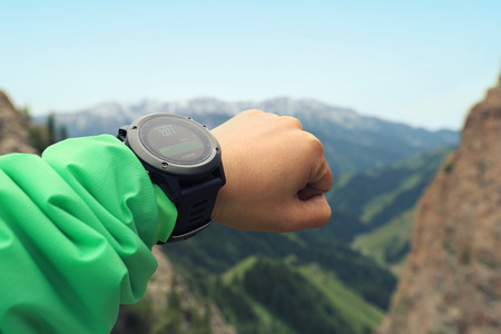 altimeter: young woman hiker checking the altimeter on sports watch at mountain peak