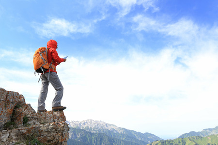 taking photo: successful woman backpacker use digital tablet taking photo on mountain peak cliff Stock Photo