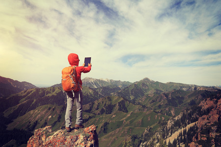 successful woman backpacker use digital tablet taking photo on mountain peak cliff Stock Photo