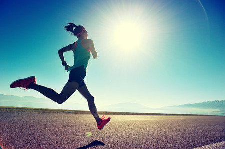 jonge fitness vrouw runner uitgevoerd op zonsopgang kust trail