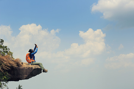 taking photo: successful woman backpacker taking photo on mountain peak cliff Stock Photo