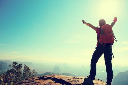 cheering woman hiker at sunrise mountain peak Stock Photo