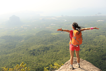 red mountain open space: free cheering woman hiker open arms at mountain peak