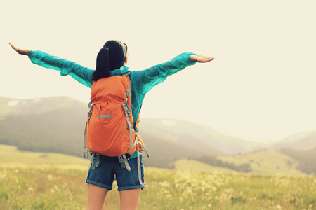 open arms: cheering young woman hiker open arms in grassland Stock Photo