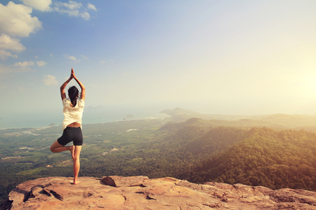 young fitness woman practice yoga at mountain peak cliff