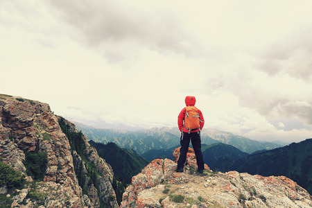 successful woman backpacker enjoy the view on mountain peak Stock Photo