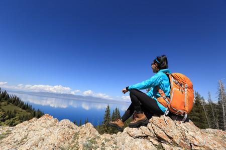 young woman backpacker hiking on beautiful mountain peak Stock Photo