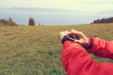 altimeter: hiker checking the altimeter on sports watch at mountain peak Stock Photo