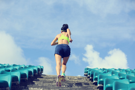 inspiring: Runner athlete running on stairs. woman fitness jogging workout wellness concept.