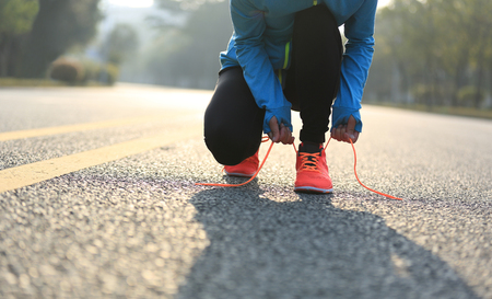 shoelaces: young woman runner tying shoelaces on road