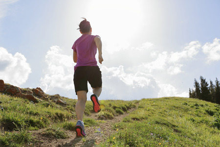 healthy lifestyle young woman trail runner running on beautiful mountain peak