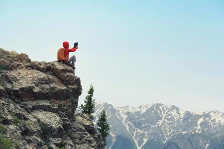 taking photo: successful backpacker taking photo on mountain peak Stock Photo