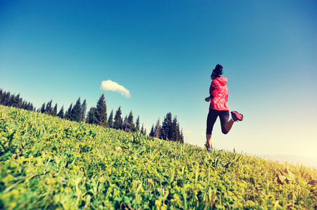 red sky: fitness young woman trail runner running on mountain peak