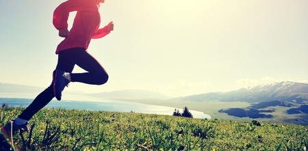young fitness woman runner running on mountain peak Stock Photo