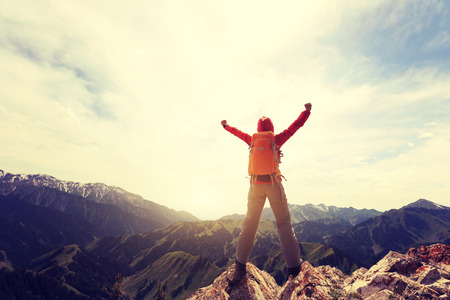 successful woman hiker open arms to mountain peak Stock Photo