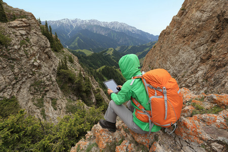 woman backpacker use digital tablet on mountain peak cliff Stock Photo