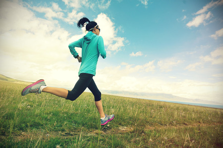 healthy lifestyle young fitness woman runner running on trail in grassland