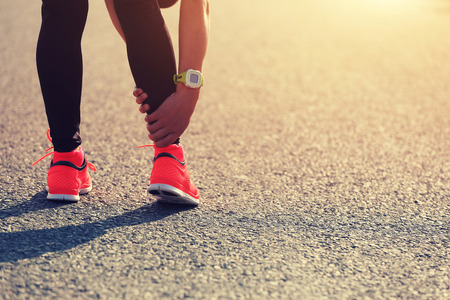 twitch: sports injury on young woman runner leg Stock Photo