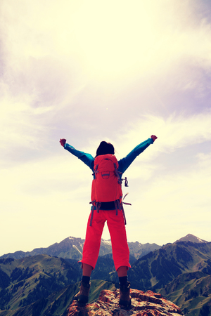 red mountain open space: cheering young woman hiker open arms on mountain top
