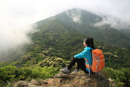 young woman backpacker on spring forest mountain peak