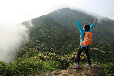 young woman backpacker open arms on spring forest mountain peak