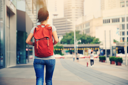 young asian woman walking on city street Foto de archivo