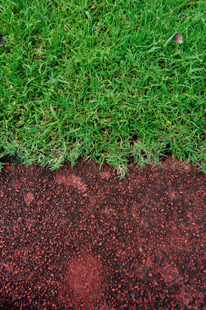 way of living: red running track and green grass in stadium