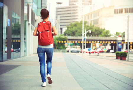 young asian woman walking on city street Stock Photo