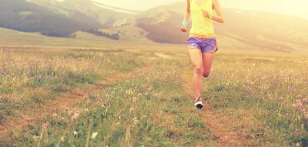 草地で実行されているヘルシー若いフィットネス女性ランナー