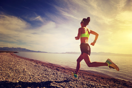 gezonde jonge fitness vrouw trail running op zonsopgang kust