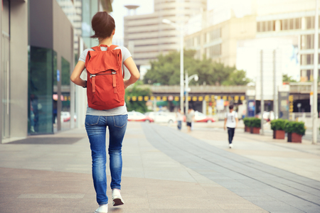 bookbag: young asian woman walking on city street Stock Photo