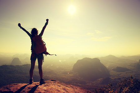 silhouette of free cheering woman hiker open arms at mountain peak Reklamní fotografie