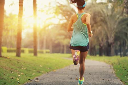 gezonde levensstijl jonge sportieve Aziatische vrouw die in tropisch park