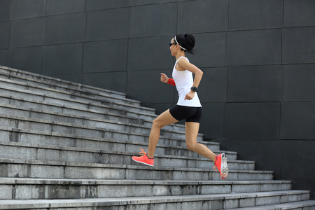 asian bodybuilder: fitness sport woman running upstairs on city stairs