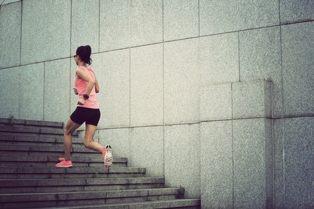upstairs: fitness sport woman running upstairs on city stairs