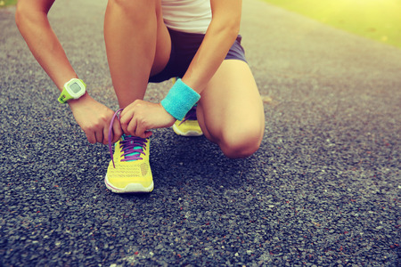 shoelaces: young woman runner tying shoelaces outdoor Stock Photo
