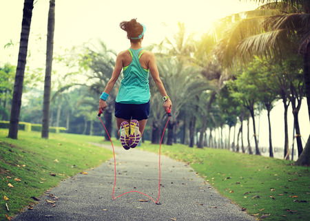 skipping rope: young fitness woman skipping rope at tropical park