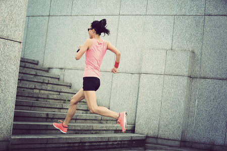 upstairs: young sport woman running upstairs on city stairs Stock Photo