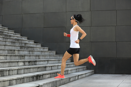 asian bodybuilder: young sport woman running upstairs on city stairs Stock Photo