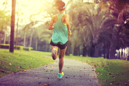 healthy lifestyle young sporty asian woman running at tropical park Stockfoto