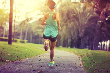 gezonde levensstijl jonge sportieve Aziatische vrouw draait op tropische park Stockfoto