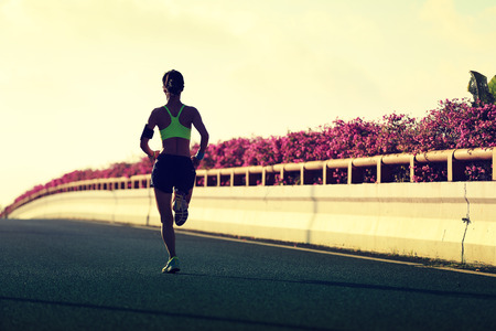 young fitness woman runner running on city road Stock Photo