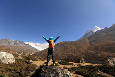 cheering young woman hiker open arms at the himalaya mountains Stock Photo