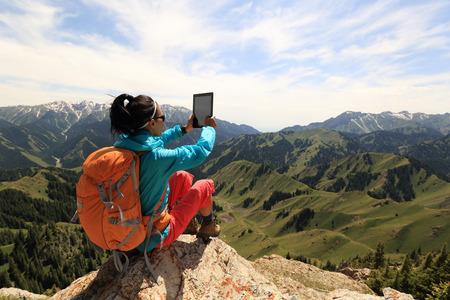successful woman hiker use digital tablet taking photo on mountain peak