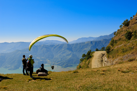 Pokhara, Nepal - November 3rd, 2016: View of a paraglider preparing to launch itself in the air. Editorial