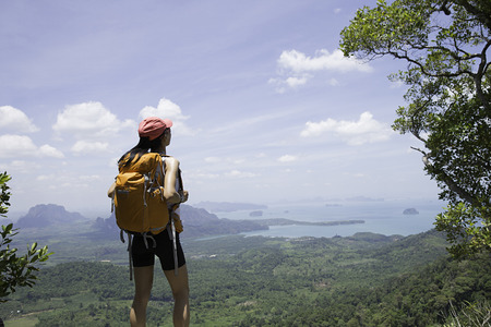 locality: young traveler with backpack standing on the mountain peak observing locality Stock Photo