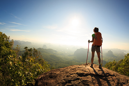 locality: young traveler with backpack on the mountain peak rock observing locality Stock Photo