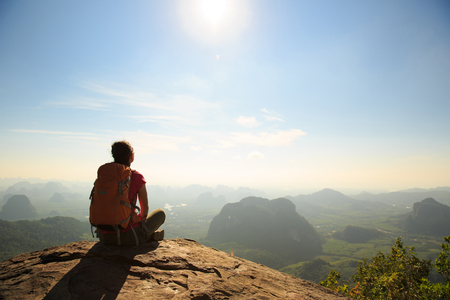 locality: young traveler with backpack sit on the mountain peak rock observing locality Stock Photo