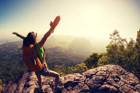 cheering woman hiker at sunrise mountain peak Foto de archivo