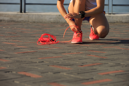 shoelace: young woman runner tying shoelace at seaside